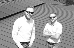 black and white photo of owners eric and derrick hoffman standing in front of solar panels installed on a metal roof.