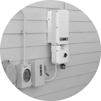 black and white photo of a solar inverter and electrical switchgear on a wall