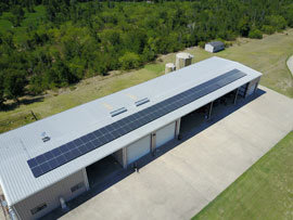 Long row of solar panels on a barn in Bastrop County