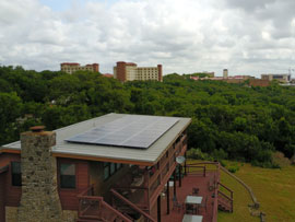 A solar array on a residential roof with Texas State University in the background